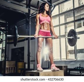 Sexy sporty female in pink sportswear holding barbell in cross fit club.