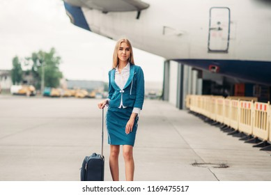 Sexy stewardess with suitcase on aircraft parking
