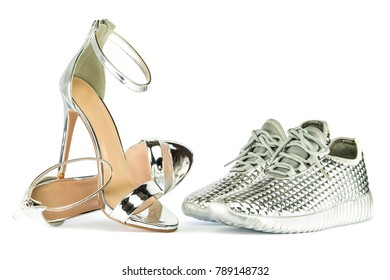 Sexy stiletto high heels with ankle strap and fashionable sneakers in shiny silver metallic color, isolated on white backgroud