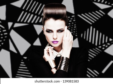 the sexy strict woman with violet lips and a fashionable  hairstyle poses in studio on creative background