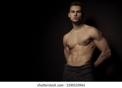 Sexy stripped sport muscle guy with grey towel on vlack isolated font background