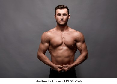 Sexy strong bodybuilder. Bodybuilder man with perfect abs, shoulders,biceps, triceps, chest.