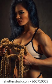 Sexy strong brunette fitness woman with big rope. Tattoo and piercings on body.