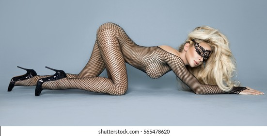 Sexy stunning blonde female model dressed in transparent body erotic and sensual mask sticking out buttocks