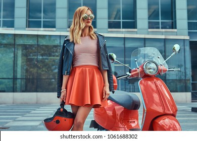 Sexy stylish blonde girl wearing a red skirt and black leather jacket and sunglasses, holding a helmet and standing near classic Italian scooter against a skyscraper.