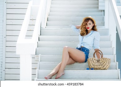 Sexy stylish girl on the summer terrace near the sea, in short denim shorts and a shirt. With make-up and hairstyle. Glasses, red lips.