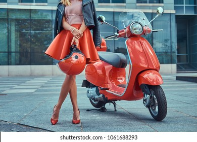 Sexy stylish girl wearing a red skirt, black leather jacket, and red shoes, holding a helmet and standing near classic Italian scooter against a skyscraper.