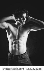 Sexy stylish strong sensual muscular young macho man with bare torso, vertical picture, toned black white image