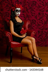 Sexy sugar skull woman sitting in a red leather chair with a red background and wood floor.
