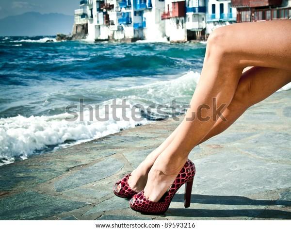 Sexy summer legs in high heels by the sea in Mykonos, Greece.