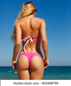 Sexy summer outdoor style beach sea vacation portrait of hot tanned back of beautiful sporty girl in pink bikini