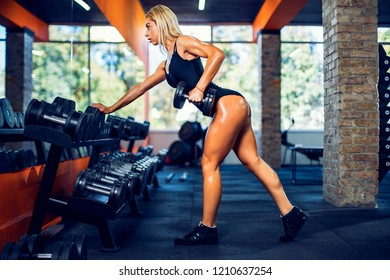 Sexy tanned athletic fitness woman doing exercises for back and posing in the gym