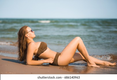Sexy tanned girl in a bathing suit and sunglasses lies on the seashore
