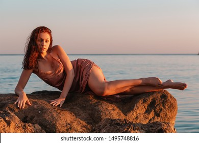 Sexy tanned woman posing reclining on coastal rocks. The sea in the background. Copy space