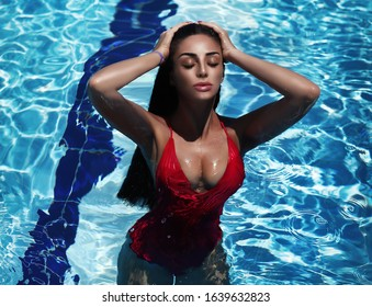 Sexy tanned woman wears bikini resting at pool on tropical beach. Brunette glamor model with perfect body relaxing near ocean. Latina girl in swimsuit at water. Summer lady at travel.