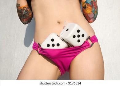 Sexy tattooed Caucasian woman in pink bikini with fuzzy dice.
