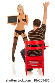 "Sexy teacher in lingerie holds a chalk board with the title of the class -- ""Sex 101"". Eager male student sits at a red school desk with arm raised high, ready to participate in class."