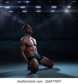 Sexy Thoughtful Athletic Man in Boxer Brief Only Kneeling on the Floor Inside a Building While Looking Up.