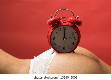 Sexy time, retro alarm clock on female ass. Beautiful naked female body with big clock on red background. Buttocks and age concept.