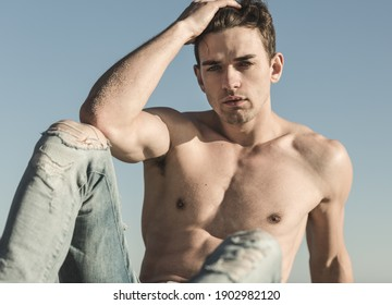 Sexy topless handsome male model posing against blue sky.