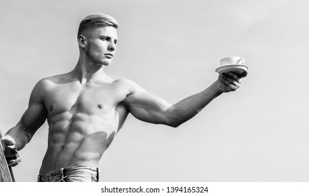 Sexy torso attractive waiter. Man muscular athlete bodybuilder offers you coffee. Macho muscular chest naked torso hold mug of fresh coffee blue sky background. Waiter bare chest hold coffee cup.