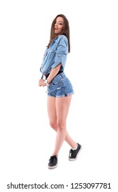Sexy tousled hair brunette in jeans shirt and shorts smiling with seductive look at camera. Full body isolated on white background.