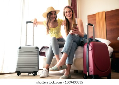 Sexy traveling girls and their luggage in a hotel room