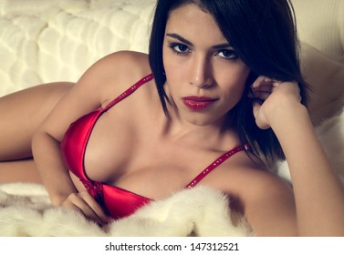 Sexy voluptuous brunette woman in red lingerie lying on her bed looking at the camera with a seductive sultry look while pouting her red lips