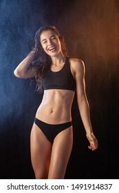Sexy wet brunette in black sports bikini and bra, posing on black background. Splashing water on background.
