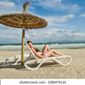 Sexy white girl on the beach sitting in the chair on a windy day