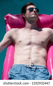 Sexy white guy with defined abs lounging in a swimming pool on a pink raft in the sun wearing aviator sunglasses relaxing, head turned to side. Hot boy hanging out in swimming pool in the summer.