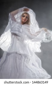 Sexy witch dressed up in white dress covered in smoke