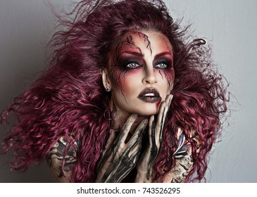 Sexy witch with Halloween make up. Beautiful flying pink hair