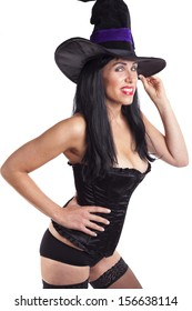 Sexy witch striking a pose, white background.
