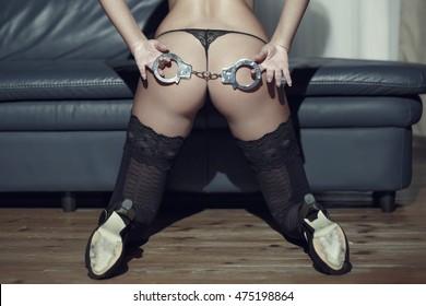 Sexy woman ass with handcuffs closeup, bdsm