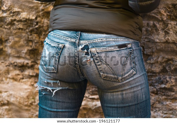 sexy woman ass in jeans on old brick wall background
