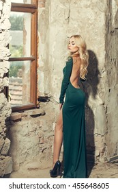 Sexy woman with attractive makeup blonde hair in splendid green dress with bare back and black high-heeled shoes posing on old stone wall near window