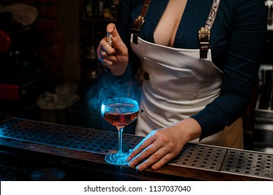 Sexy woman barman with deep neckline spraying blue-colored bitter on the elegant cocktail glass on the bar counter