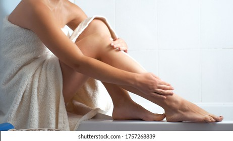 Sexy woman in bath towel sitting on bath edge and massaging her legs and feet.