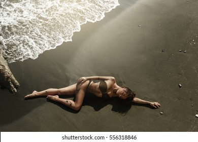 Sexy woman with beautiful body is lying on the beach beside the sea