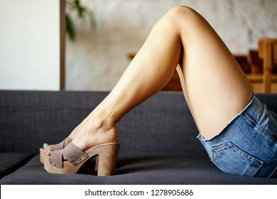 Sexy woman with beautiful slim legs lies on gray couch in denim shorts and wooden wedge heels.