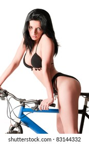 Sexy woman in bikini riding bicycle