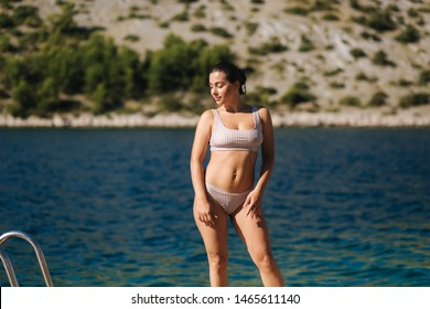 Sexy woman in bikini stand in front of beautiful blue water. Summer vocation on the sea