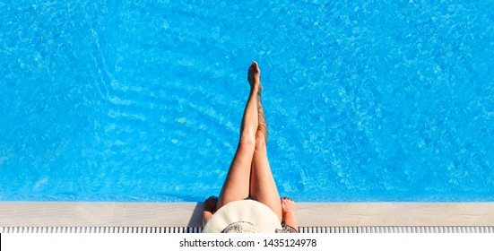Sexy woman in bikini and sunhat relaxing in swimming pool. Top view of lady in swimsuit and hat in luxury hotel resort poolside. Summer holiday vacation lifestyle. Hot female legs in water.
