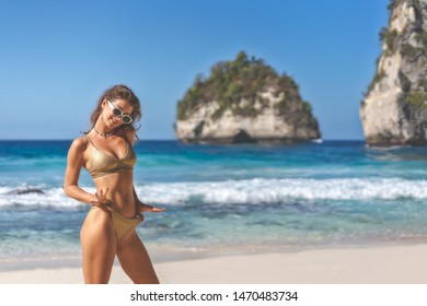 Sexy woman in bikini wearing sunglasses playful on paradise tropical beach having fun playing.