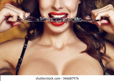 Sexy woman bite handcuffs, red lips, bdsm