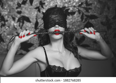 Sexy woman bite whip in lace blindfold, black and white selective coloring with red, bdsm
