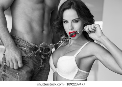 Sexy woman biting handcuffs at macho lovers body black and white with red lips, bdsm