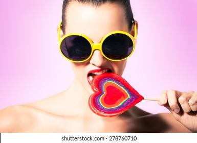 Sexy woman biting lollipop.