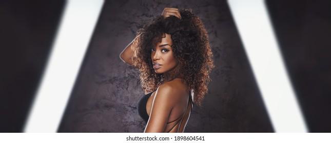 Sexy Frau in schwarzem Bikini, die vor der Kamera steht